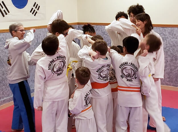 rouleau holley's tae kwon do kids students gathered, giving high elbows to instructor