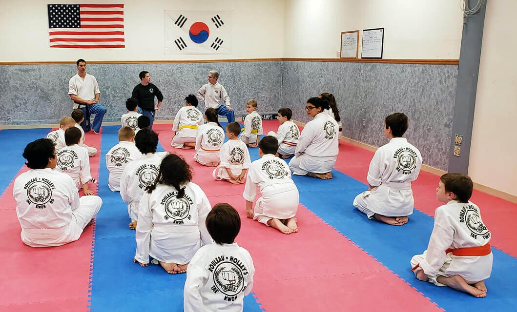rouleau holley's martial arts students seated on floor, listening to instructor